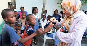 A volunteer with Hizmet organization Kimse Yok Mu with victims of the earthquake in Haiti.