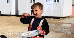 A Young Syrian refugee eating a warm meal provided by Hizmet relief organization Kimse Yok Mu.